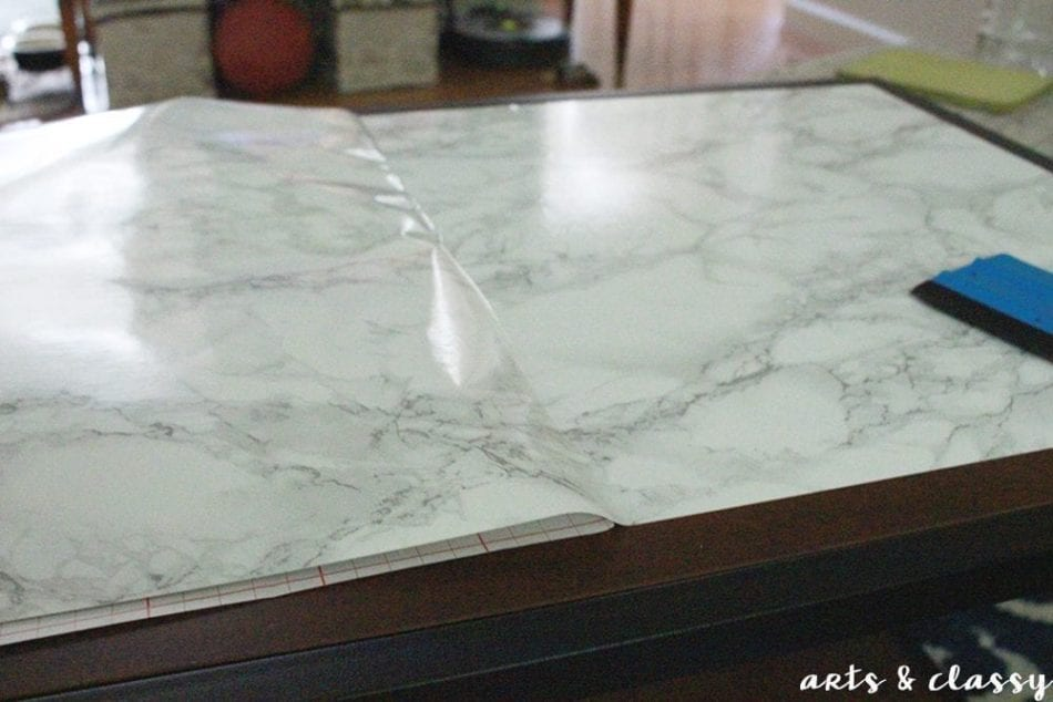 DIY Faux Marble Coffee Table Makeover applying the marble contact paper
